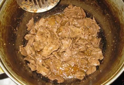 Как только покроется мясо легкой корочкой, убавляем огонь, перемешиваем и жарим говядину около 20-25 минут.