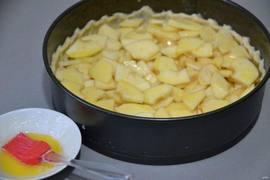 На ореховую крошку выложите яблоки, смажьте растопленным сливочным маслом, отправьте в духовку при температуре 190 градусов на 20 минут.