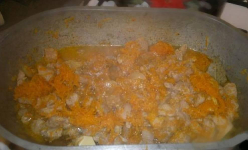 5. Теперь добавьте в утятницу лук, морковь, 3 зубчика чеснока и 3 лавровых листика. Перемешайте, добавьте кипяченой воды и оставьте тушиться еще на минут 5-7.