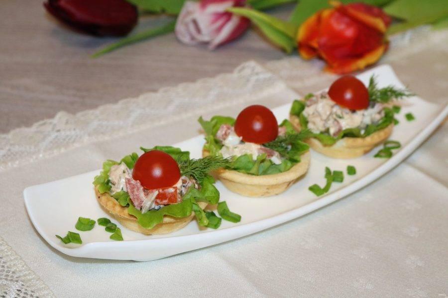 Сверху украсьте зеленью и половинками томатов черри.