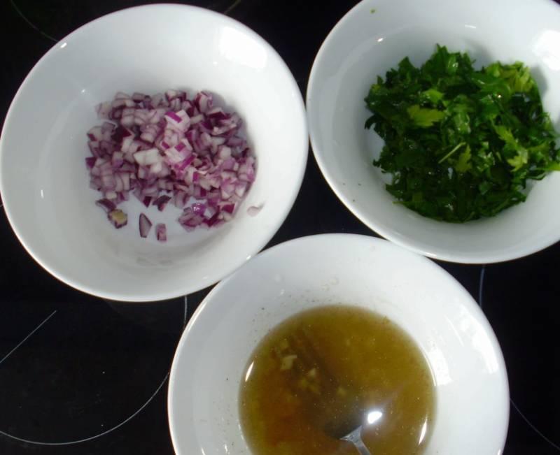 Мелко нарезаем лук и петрушку. Смешиваем масло, уксус, раздавленный чеснок, соль, сахар и перец для маринада.