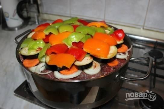 И повторяем слои: помидоры, мясо, репчатый лук, морковь, баклажаны, молотая паприка, чеснок, перец. Мясо и баклажаны нужно немного посолить.