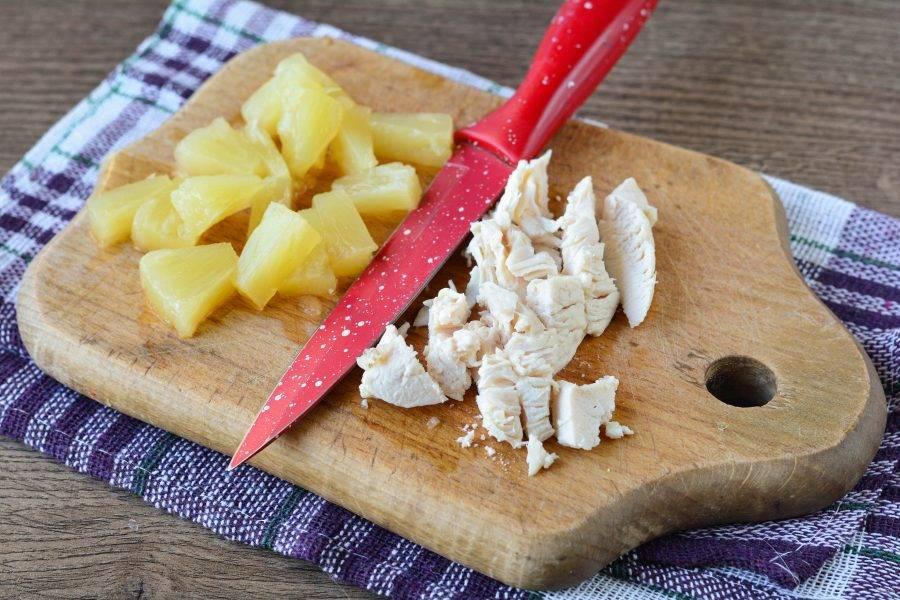 Для начинки нарежьте средними кусочками отварное куриное филе и консервированные ананасы.
