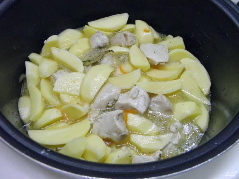 """Добавьте к обжаренному мясу картофель, чеснок, соль, лавровый лист, специи. Залейте водой так, чтобы картофель был почти покрыт. Закройте крышку и выберите режим """"каша"""" или """"суп"""". Время тушения — 40 минут."""