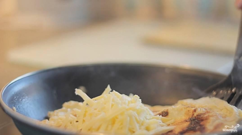 В это время сыр натрите на терке. Как справитесь, выложите его на одну половину омлета и накройте другой.