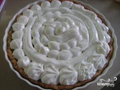 Достаем пирог из духовки и с помощью кондитерского мешка покрываем поверхность пирога белковой массой.