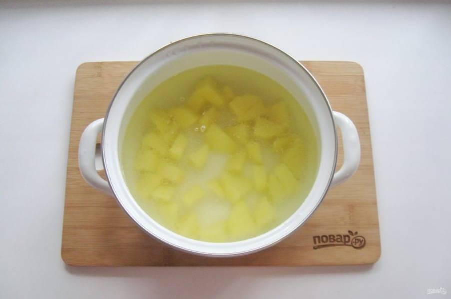 Картофель очистите, помойте и нарежьте кубиками. Выложите в кастрюлю и залейте бульоном. Поставьте кастрюлю на плиту и начинайте варить суп.