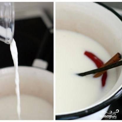 Берем сотейник, кладем в него половину палки ванили, чили перец и корицу. Заливаем все это молоком - и на средний огонь.