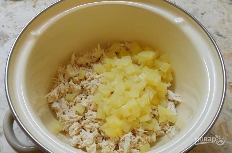 1.Курица у меня уже отваренная, поэтому нарезаю его небольшими кубиками и отправляю в кастрюлю. Консервированные ананасы нарезаю кубиками и добавляю к курице.