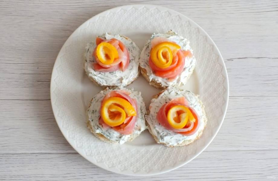 Ломтики лимона скрутите в цветочек. Установите в серединку красной рыбы.