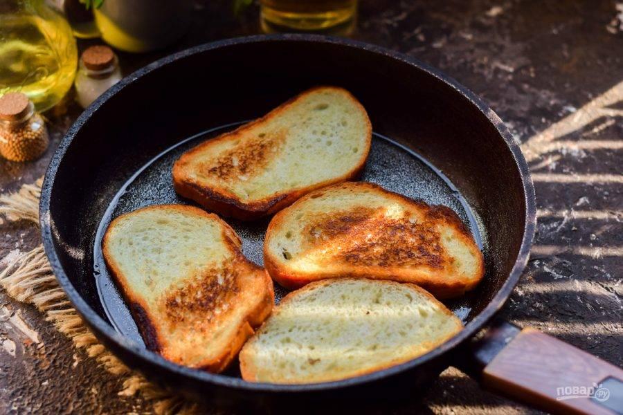 Хорошо прогрейте сковороду, слегка смажьте сливочным маслом. Переложите ломтики батона в сковороду, поджарьте с обеих сторон до румяности.