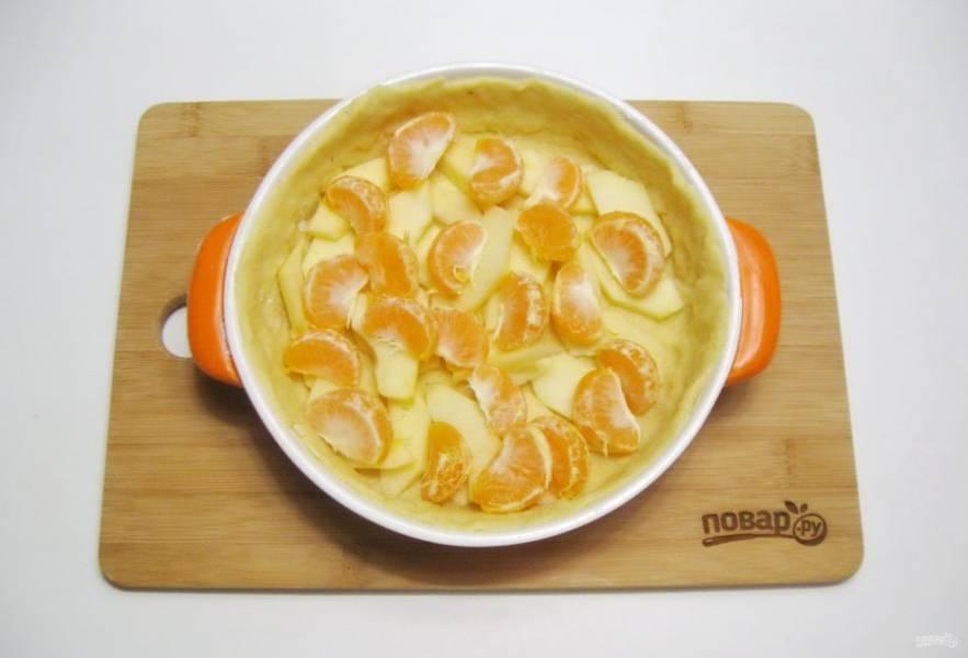 Яблоки помойте, очистите и нарежьте пластинками. Мандарины очистите и разделите на дольки. Выложите фрукты на тесто.