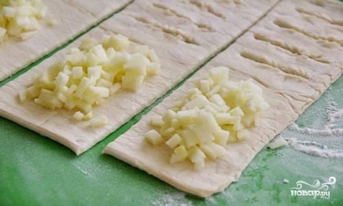 На кусочки теста, а именно — на ту сторону, где нет надрезов, положите достаточное количество измельченных яблок, сверху на них насыпьте 1-2 чайные ложки сахарного песка.