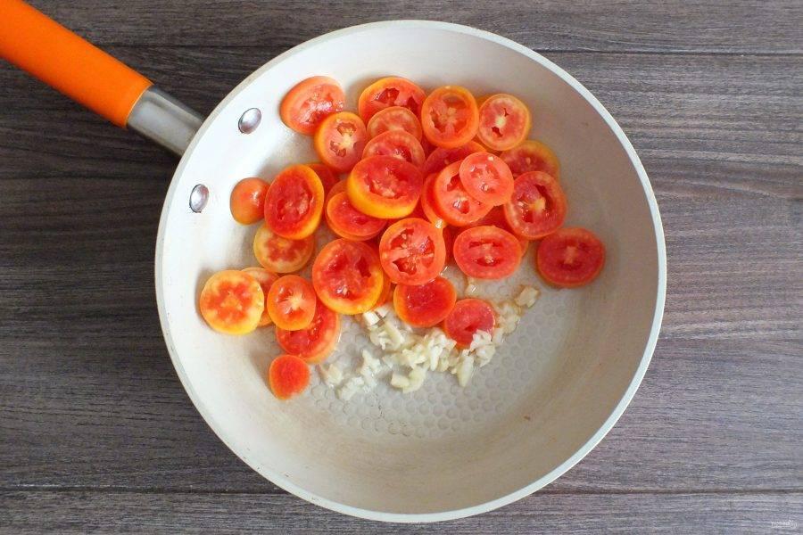 В сковороде разогрейте 30 мл. растительного масла. Переложите в неё помидоры и чеснок. Обжаривайте в течение 3-4 минут, постоянно помешивая.