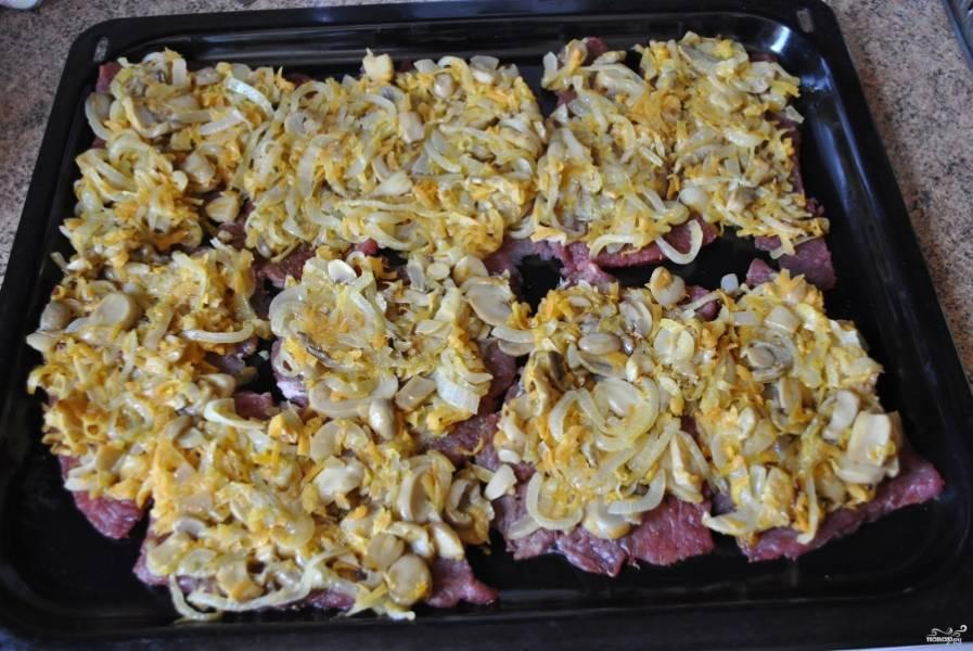 На противень выложите мясо, на каждый кусок - грибную смесь.