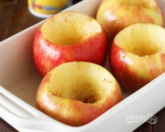 1. Яблоки вымойте, аккуратно вырежьте сердцевину. Выложите их в жаропрочную форму, смазанную при помощи кисточки растительным маслом или застеленную пергаментом. Присыпьте корицей.