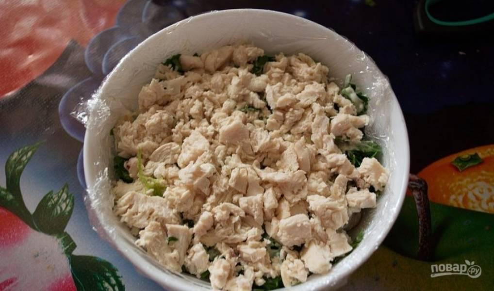 Затем смажьте зелень майонезом. Разберите курицу на волокна, когда она остынет. Положите её следующим слоем.