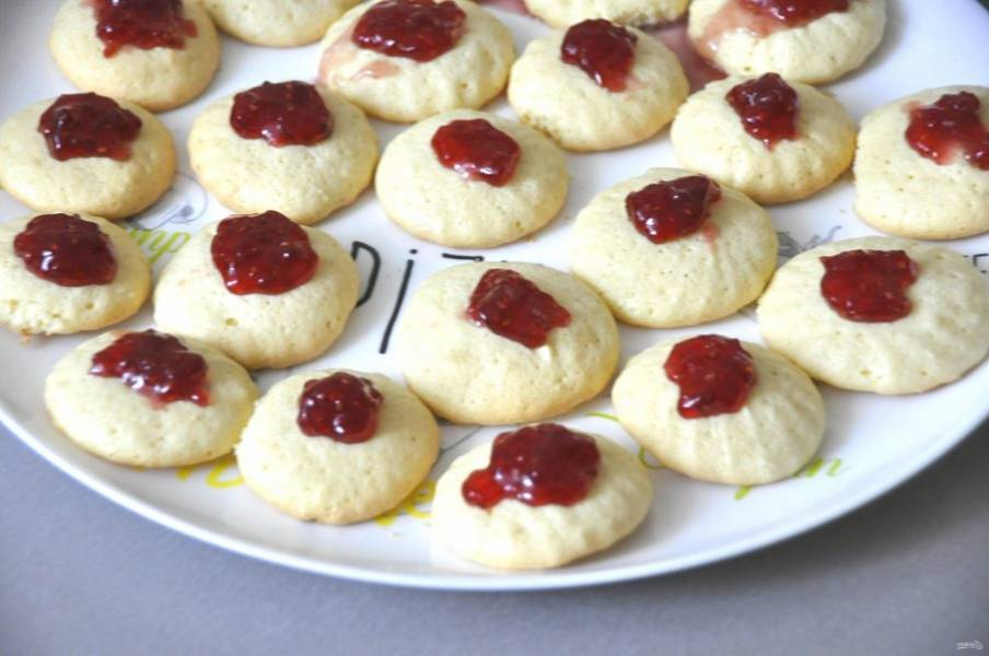 Выложите на печенье ягодный джем, который должен быть достаточно густым. Перед покрытием шоколадом, уберите ненадолго печенье в холодильник или в морозильную камеру.