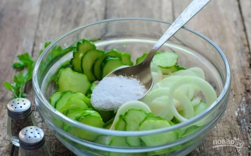 Огурцы вымойте и обсушите. Обрежьте у них с обеих сторон кончики. Нарежьте огурцы на кружочки. Затем очистите лук, нарежьте его колечками. Добавьте к овощам соль и все тщательно перемешайте.