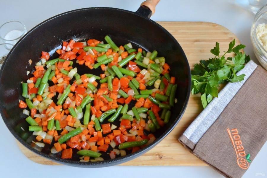 4. Когда овощи будут почти готовы, добавьте к ним промытый рис и обжарьте минуту.