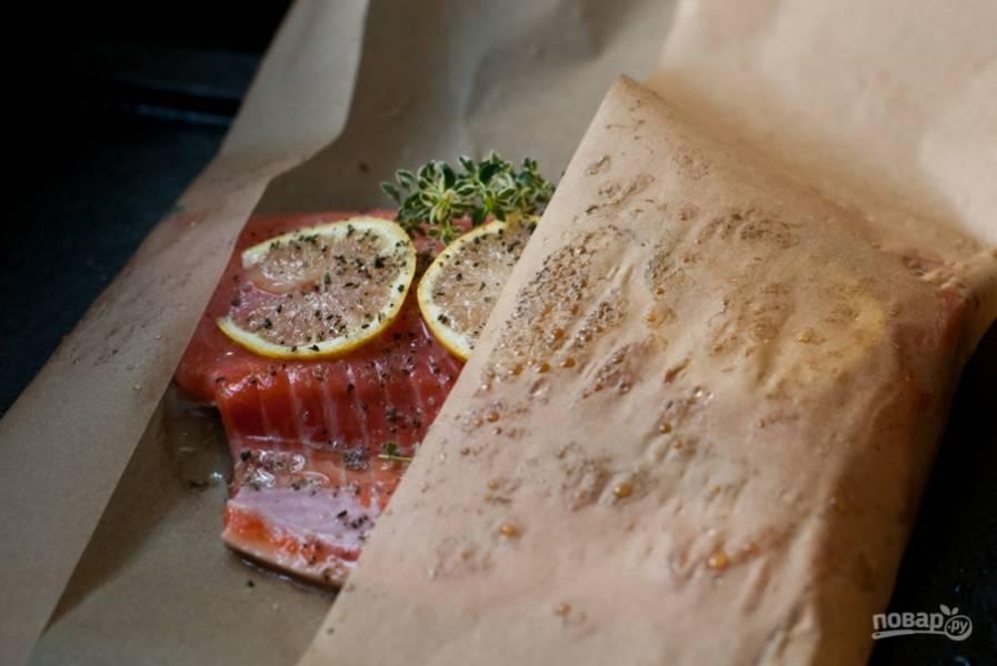 Сбрызните лосось маслом авокадо. Если его нет, ипользуйте оливковое масло хорошего качества. Заверните край пергаментного листа.