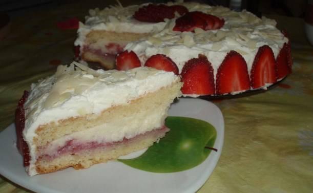 Накройте другим коржом. Оставьте торт в холодильнике на ночь или хотя бы на 6 часов (для пропитки). Готовый бисквитный торт с клубникой и заварным кремом обмажьте взбитыми с сахаром и ванильным сахаром сливками (2 ст.л. сахара и 1 ч.л. ванильного сахара). А украсить можете лепестками миндаля.