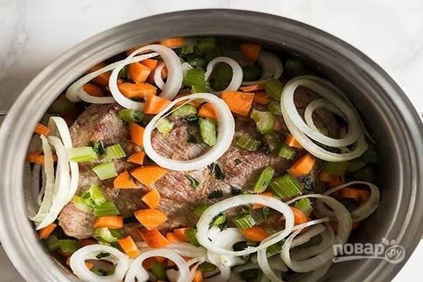 Когда кусок мяса хорошо обжарится, добавьте нарезанные овощи, гвоздику и лавровый лист.