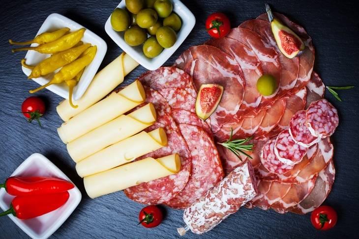 В данном варианте сыр нарезается прямоугольными ломтиками, которые скручиваются в рулетики. Колбасу и мясо режем как обычно. Аккуратно складываем все на широкое блюдо, украсив по бокам оливками и перчиком. Приятного аппетита!
