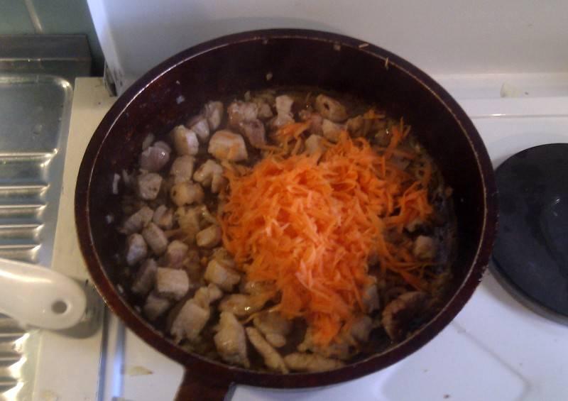 Морковь чистим и трем на крупной терке, перекладываем ее на сковородку и жарим все вместе еще пару минут.