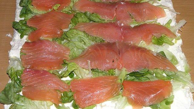 На листья салата равномерно разложите кусочки рыбы.