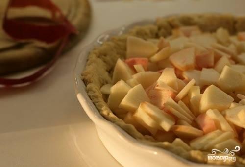 Яблоки тщательно вымойте, удалите у них сердцевину и косточки. Нарежьте их на небольшие, произвольной формы кусочки. Фрукты лучше выбирать кисло-сладких сортов с ярко выраженным вкусом и ароматом. Выложите яблоки на выпеченный корж.