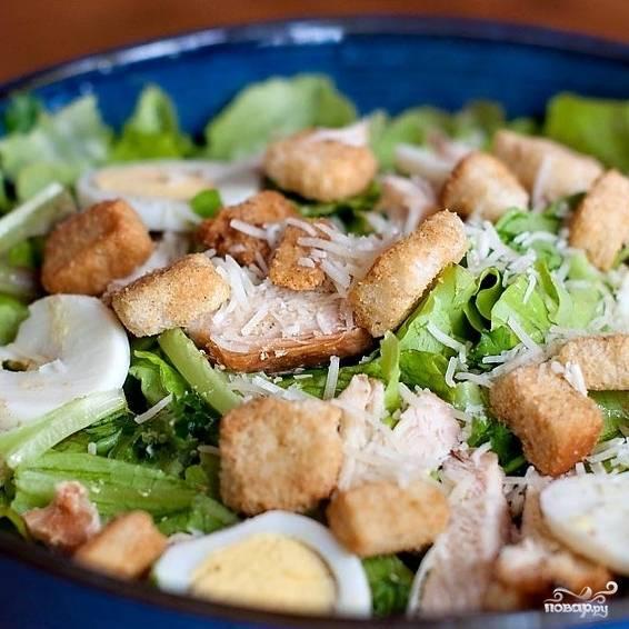 Дело за малым. На дно салатницы выкладываем листья салата и петрушку, добавляем соус для цезаря и немного пармезана, перемешиваем. Сверху выкладываем нарезанные яйца, курицу и сухарики, а затем присыпаем все блюдо пармезаном. Готово!