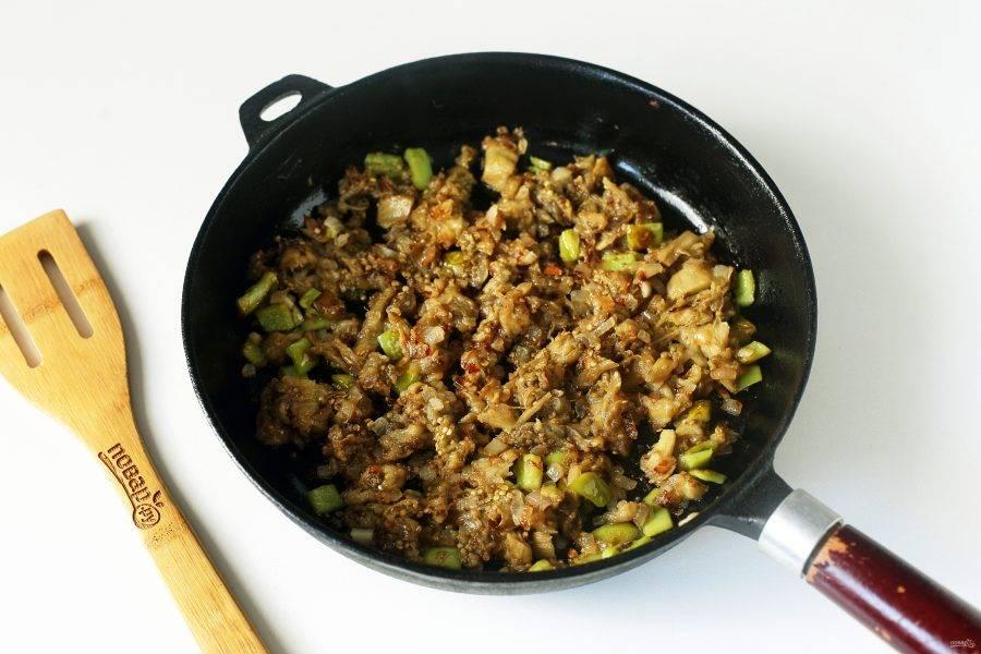 Добавьте измельченную мякоть баклажанов и продолжайте готовить еще около 2-3 минут.