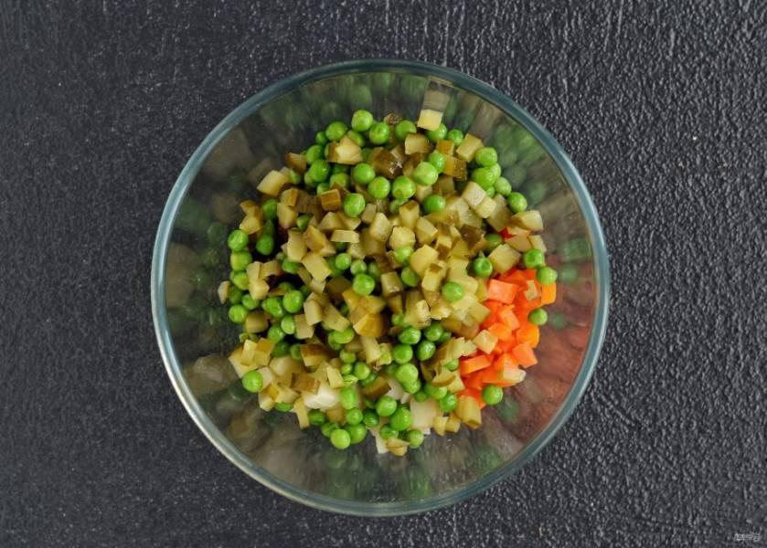 Соленые огурцы тоже нарежьте на мелкие кубики, зелёный горошек разморозьте. Переложите в миску.