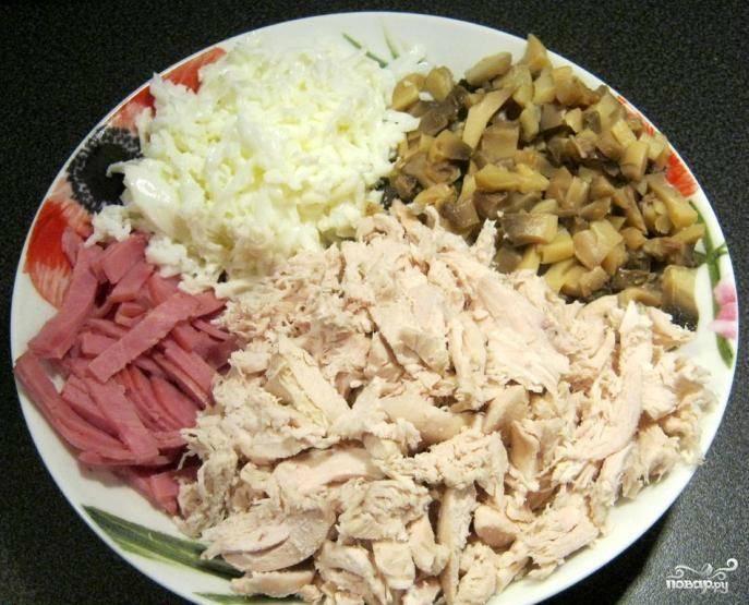 Вареное мясо курицы отделяем от костей и мелко нарезаем, буквально разбирая его на волокна. Ветчину нарезаем тонкой соломкой, а шампиньоны – небольшими кусочками.