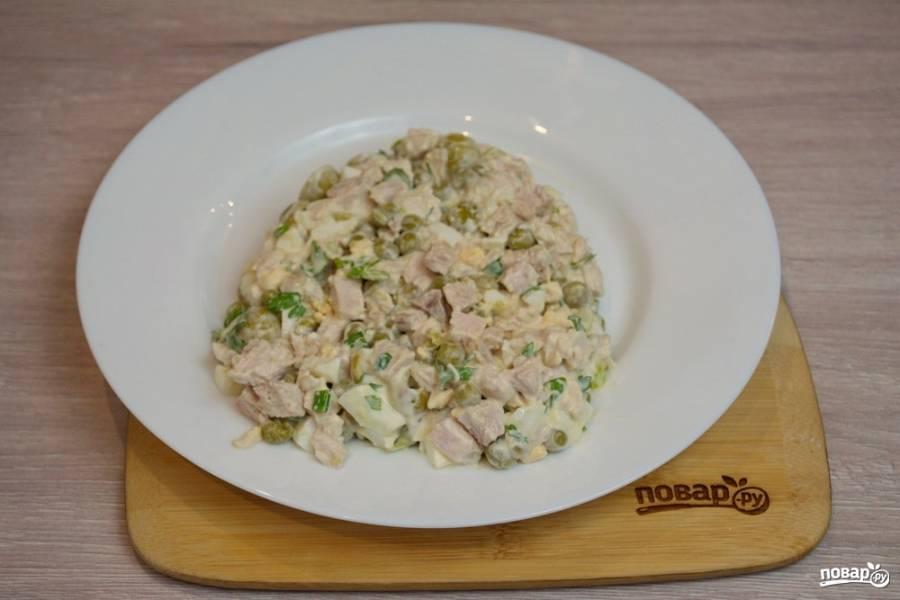 На плоское блюдо выложите салат. Придайте ему форму головы петуха.