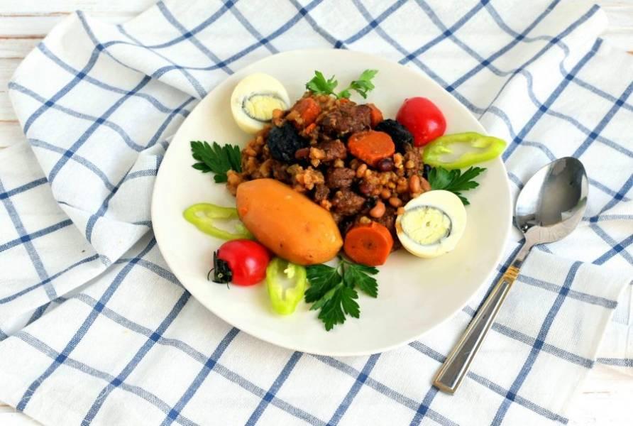 По окончанию работы мультиварки переведите ее в режим Сохранения тепла еще на полчаса. И можно подавать чолнт к столу. По тарелкам раскладывают картофель и мясо с овощами и перловкой, непременно каждому кладут очищенное яйцо. Отдельно к чолнту подают соленые или маринованные, а также свежие овощи.