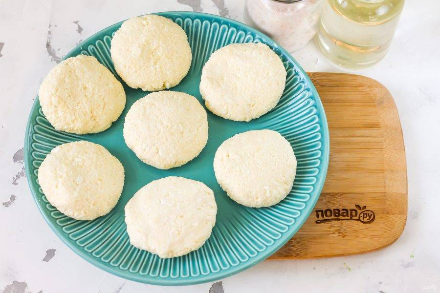 Смочите руки в воде и сформируйте из части творожной массы заготовку сырника. Таким же способом приготовьте остальные заготовки.