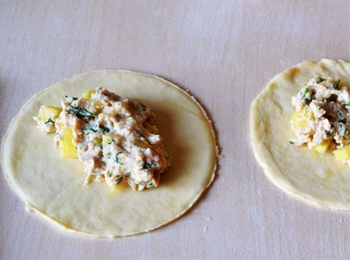 Разделите тесто на части, раскатайте в пласт, в центр выложите начинку. Она состоит из порезанного кубиками картофеля и пропущенной через мясорубку вареной курятины с луком и зеленью.