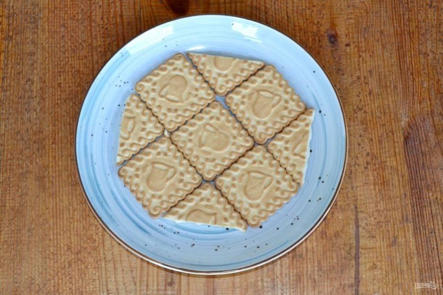 На тарелку выложите печенье. Если печенье квадратное, можно вот таким образом подрезать его.