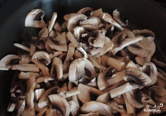 Шампиньоны промойте и нарежьте пластинками. Обжарьте их в масле на сильном огне в течение 10 минут.