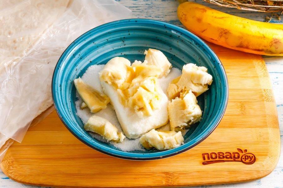 В глубокую емкость выложите творог, всыпьте сахар. Очистите банан от кожуры и разломите на части, добавьте в емкость. По желанию всыпьте ванильный сахар или другой ароматизатор. Тщательно помните и перемешайте начинку.