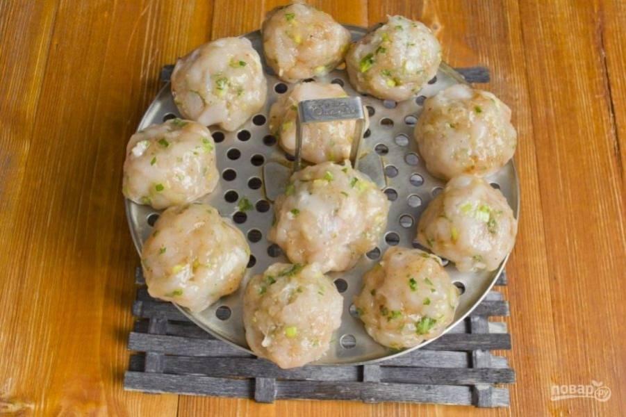 Затем влажными руками сделайте фрикадельки. Выложите их в пароварку и сбрызните маслом.