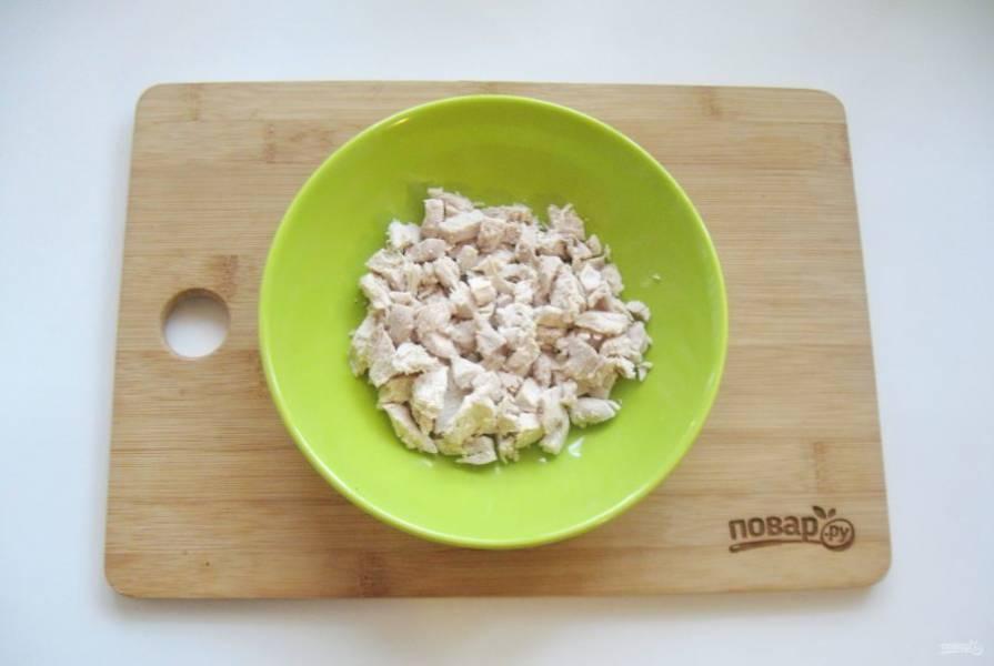 Вареную куриную грудку охладите и мелко нарежьте. Выложите в тарелку первым слоем салата. Можно немного поперчить по вкусу.