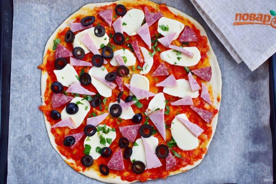 8.    Разложите сверху начинку: тонко нарезанные ломтики колбасы, ветчины, моцареллы, листики базилика и оливки.