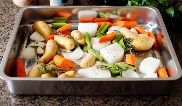 2. Молодой картофель можно даже не чистить, достаточно лишь тщательно его вымыть. Овощи очистить и нарезать крупными кусочками. Выложить на дно формы для запекания.