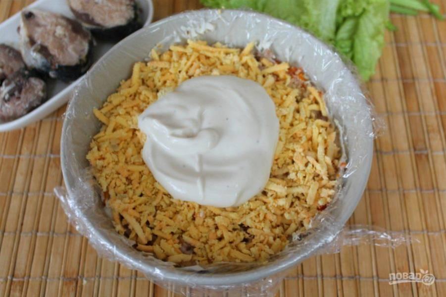 Далее добавляем в салат тертый желток и вновь тонкий слой майонеза.