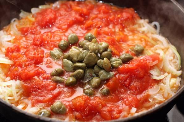 6. С помидоров снимите кожицу (можно также использовать готовый томат), выложите их к луку. Добавьте каперсы, затем все аккуратно перемешайте и тушите на среднем огне 3-5 минут.