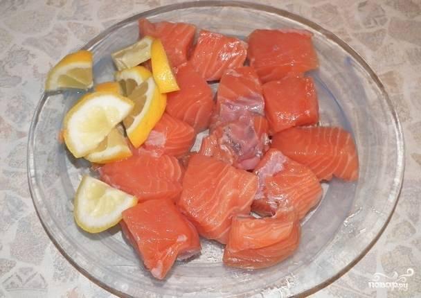 Порезать рыбу и лимон на куски.