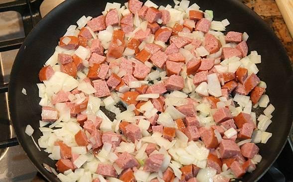 5. Пока готовится мясо можно заняться соусом. Очистить и нарезать небольшими кубиками луковицу. Сосиски или колбаски нарезать и отправить все на сковороду.